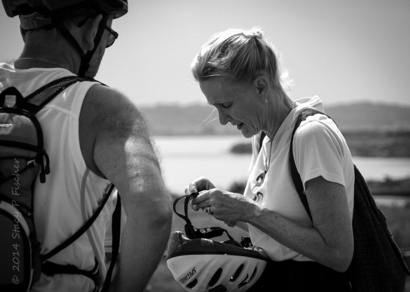 Older woman getting ready to put on her bike helmet as her male bicyling partner waits and watches.