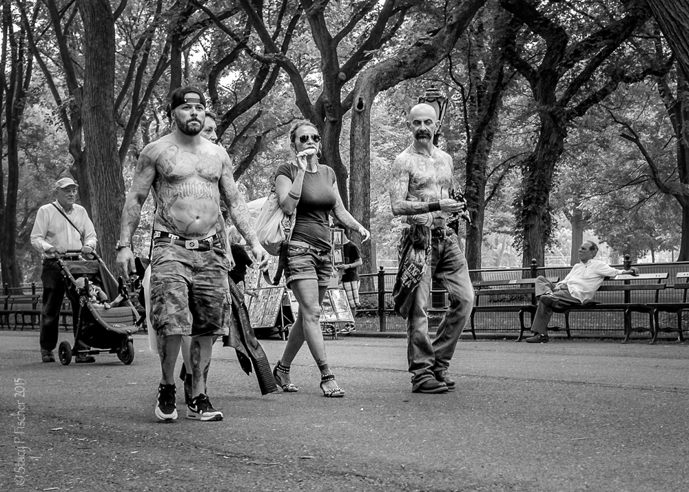 A trio of tattooed pedestrians walking in Central Park