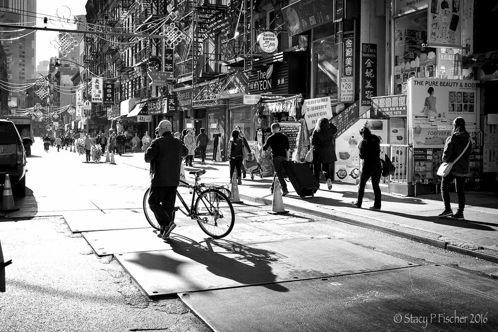 Long shadows of bicyclist on Mott Street, Chinatown, New York City