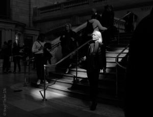 shaft of light highlights woman's face as she descends stairs at Grand Central Station, NYC